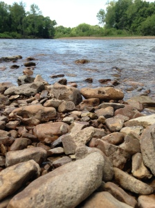 The gentle river flow across the rocky shore line.