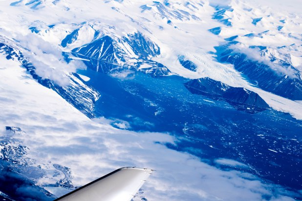 Mountain ranges stop abruptly, sinking to the deep blue waters of Antarctica.
