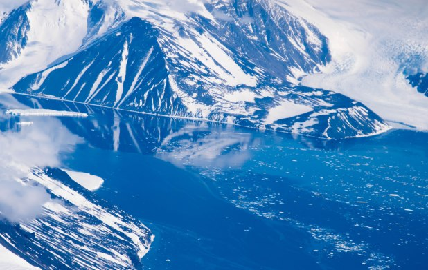 Reflections from the still sea water of an Antarctic inlet.