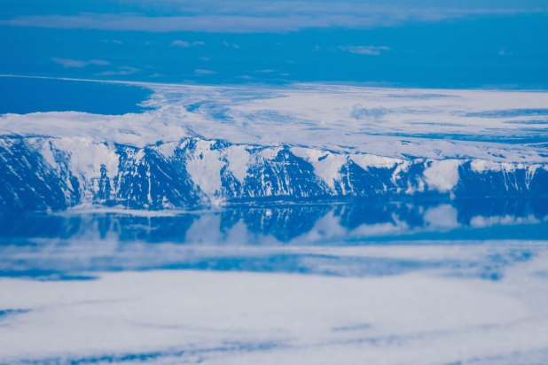 Mountain ranges of Antarctica meet the deep blue sea.